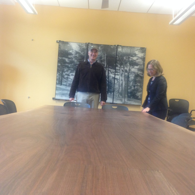 The new conference table made from the same black walnut, shown off by Ned Friedman, arboretum director, and Faye Rosin, director, research facilitation.